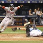 Dustin Pedroia, left, scored a run on a fielding error by Tampa Bay Rays catcher Luke Maile.